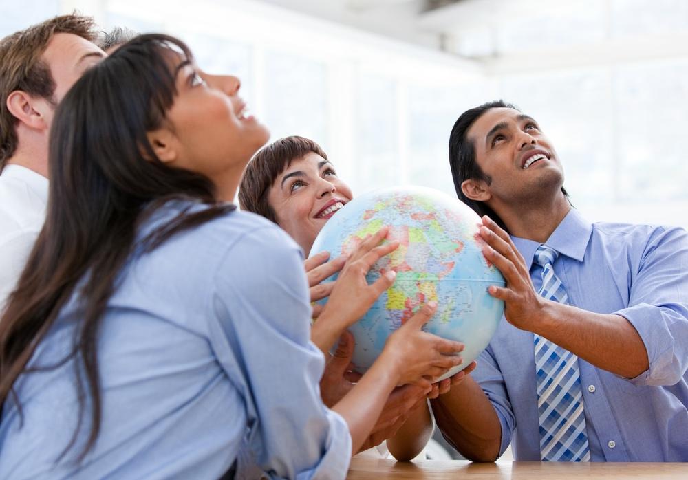 International business team holding a terrestrial globe in a meeting.jpeg