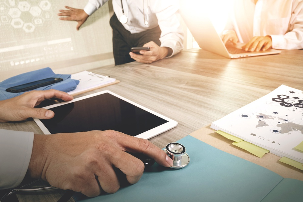 Medicine doctor hand working with modern computer and digital pro tablet with blank screen with his team on wooden desk as medical concept.jpeg