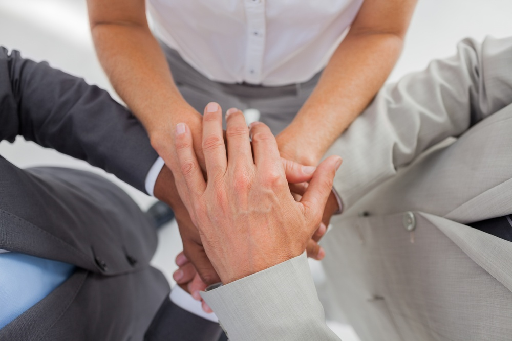 Business people gathering their hands together in the workplace.jpeg
