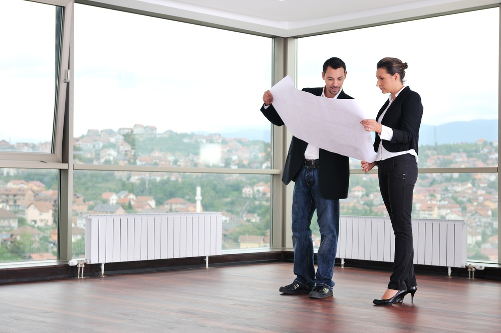 young architect group in big bright modern new apartment looking blueprints and building plans.jpeg