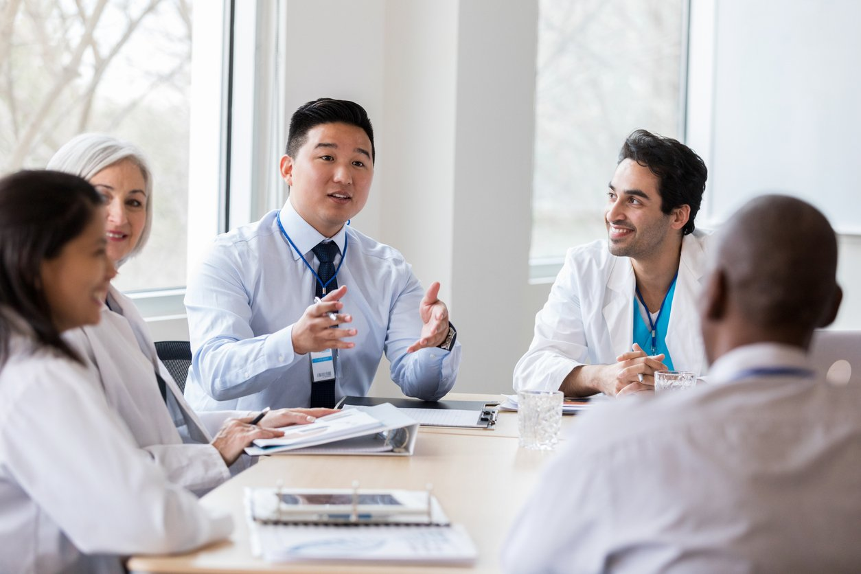Young male hospital administrator gestures while discussing a topic with doctors and other people in hospital management.