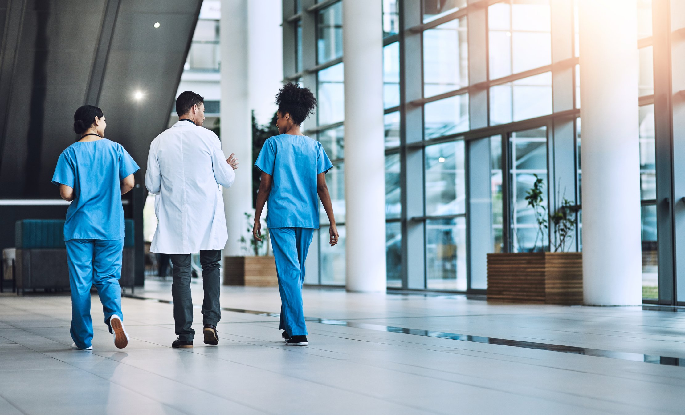 hospital staff and practitioners walking through a hospital lobby