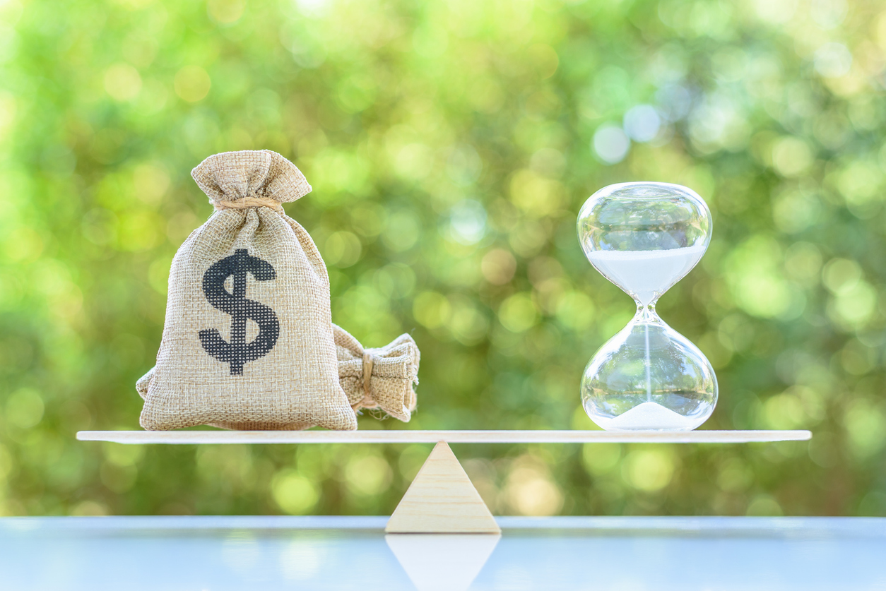 Dollar bags and a sand clock/hourglass on a balance scale in equal position