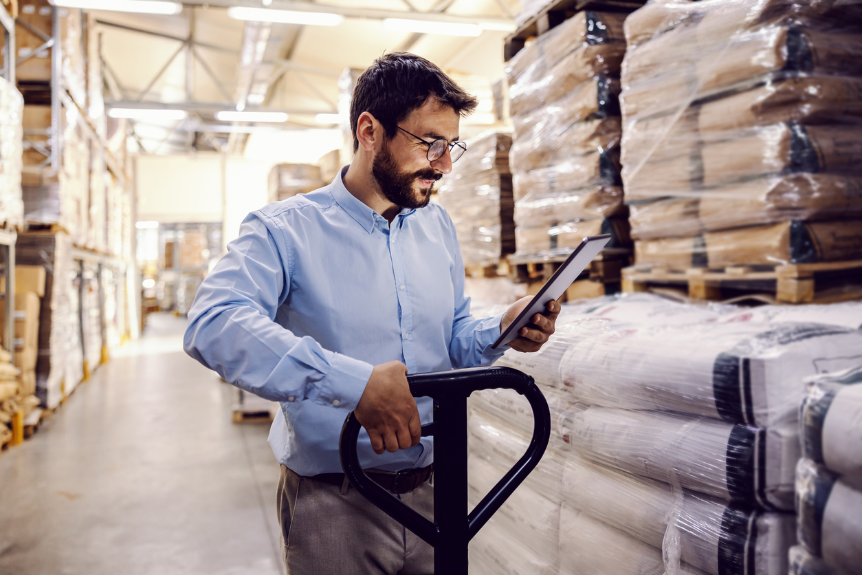 Young hardworking supervisor pushing forklift while looking at tablet.