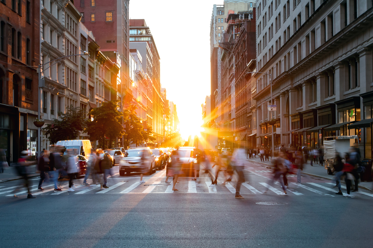 Crowds of busy people walking through the intersection of 5th Avenue and 23rd Street in Manhattan, New York. City with bright sunset background