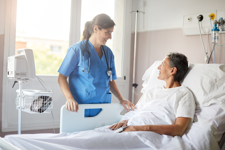 nurse and patient smiling at one another