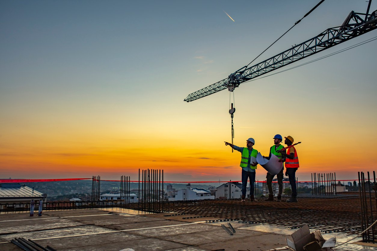 Three construction workers in uniform standing at construction site with crane in background, discussing building plans while holding blueprint at sunset under the tower crane.