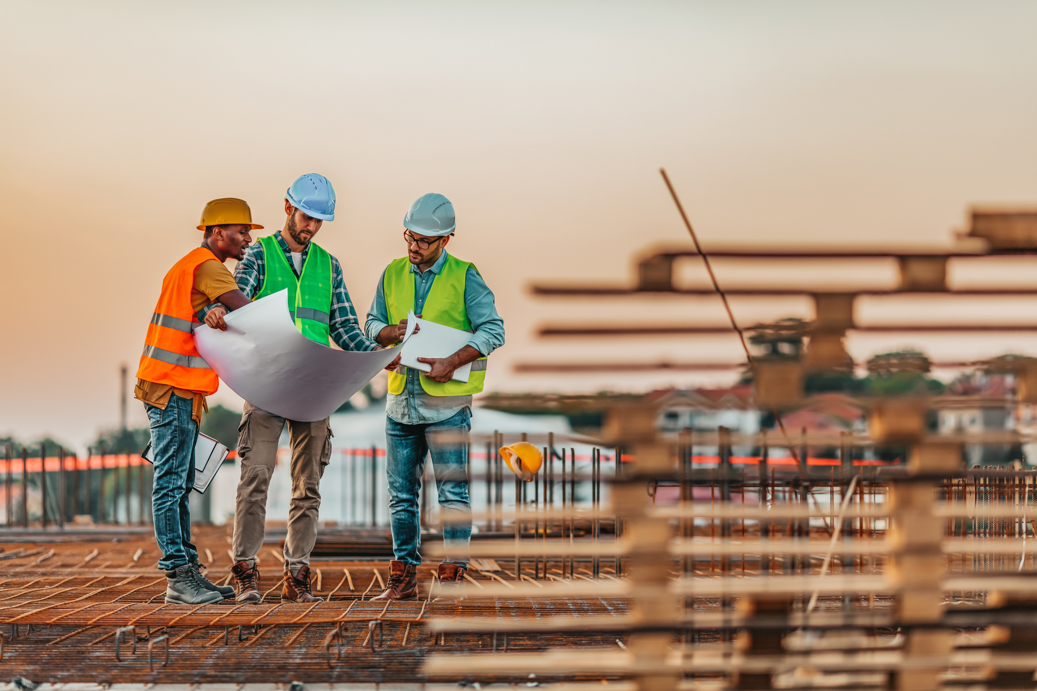 Photo of Teams engineer looking construction worker in a building site at sunset.