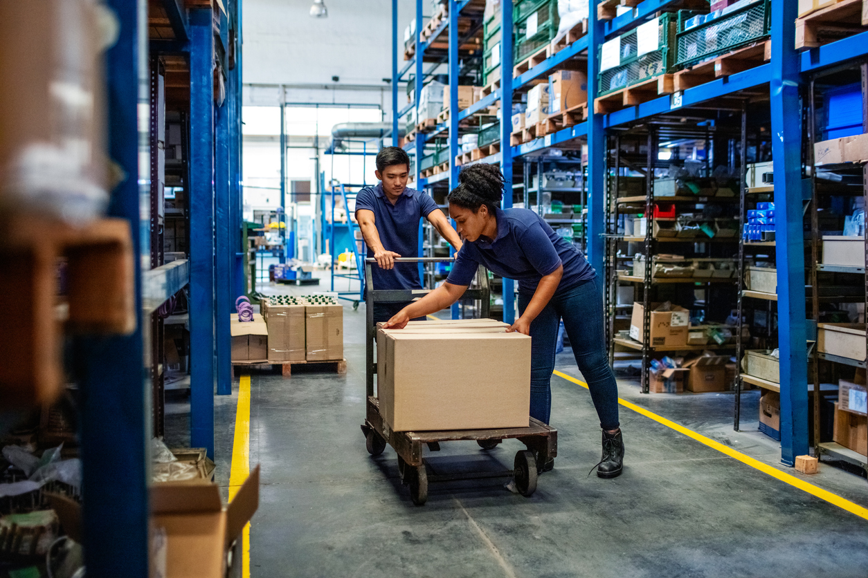 Distribution warehouse workers moving boxes in plant. Man and woman in uniform working in a large warehouse.