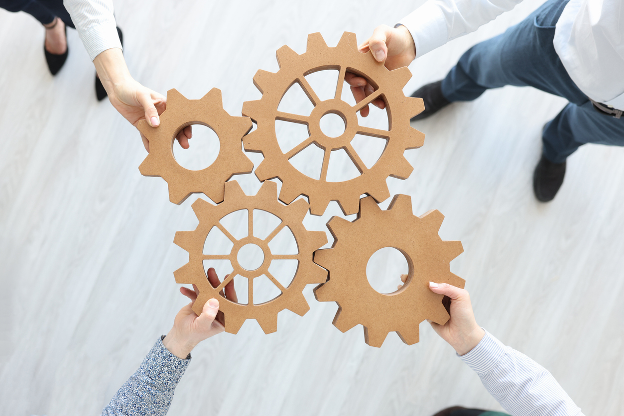 Group of business people stacking wooden gears top view.