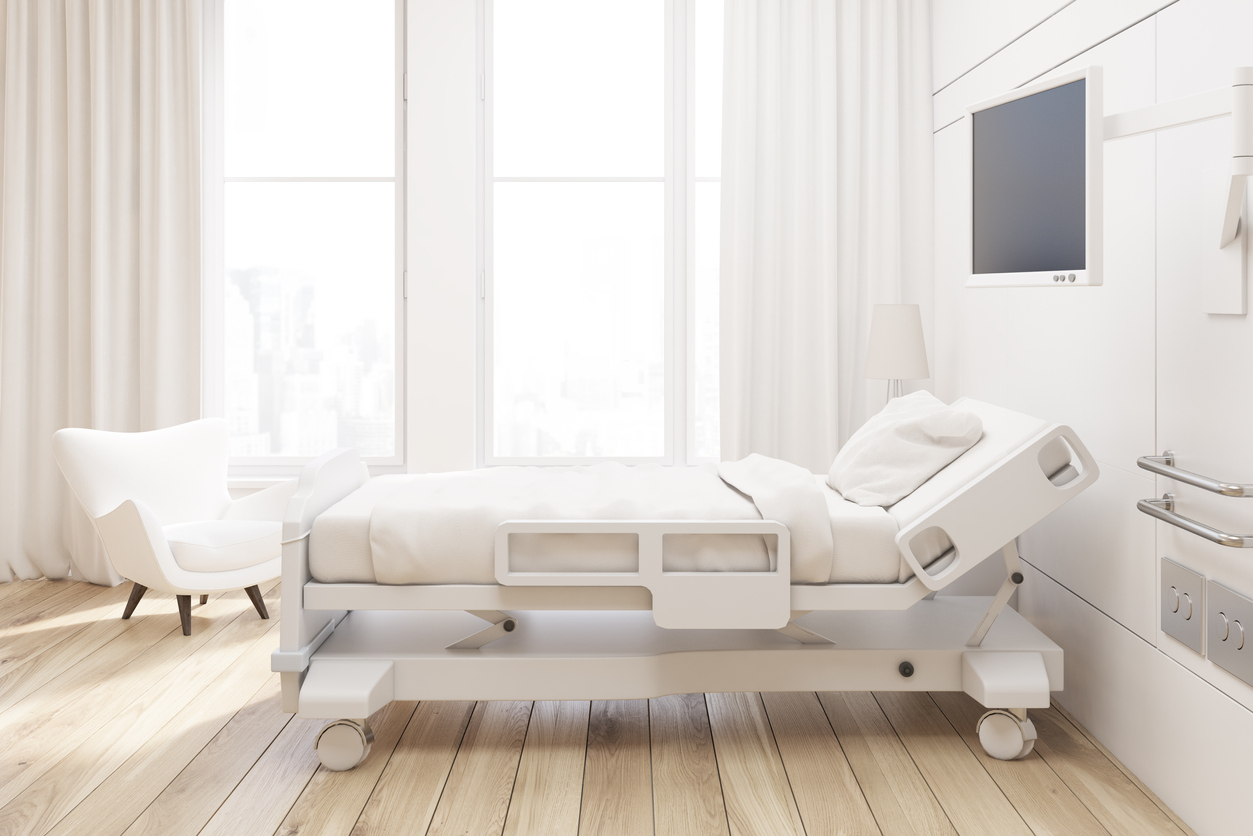 Side view of a hospital ward with a bed, a tv set, a white armchair and curtains on large windows.