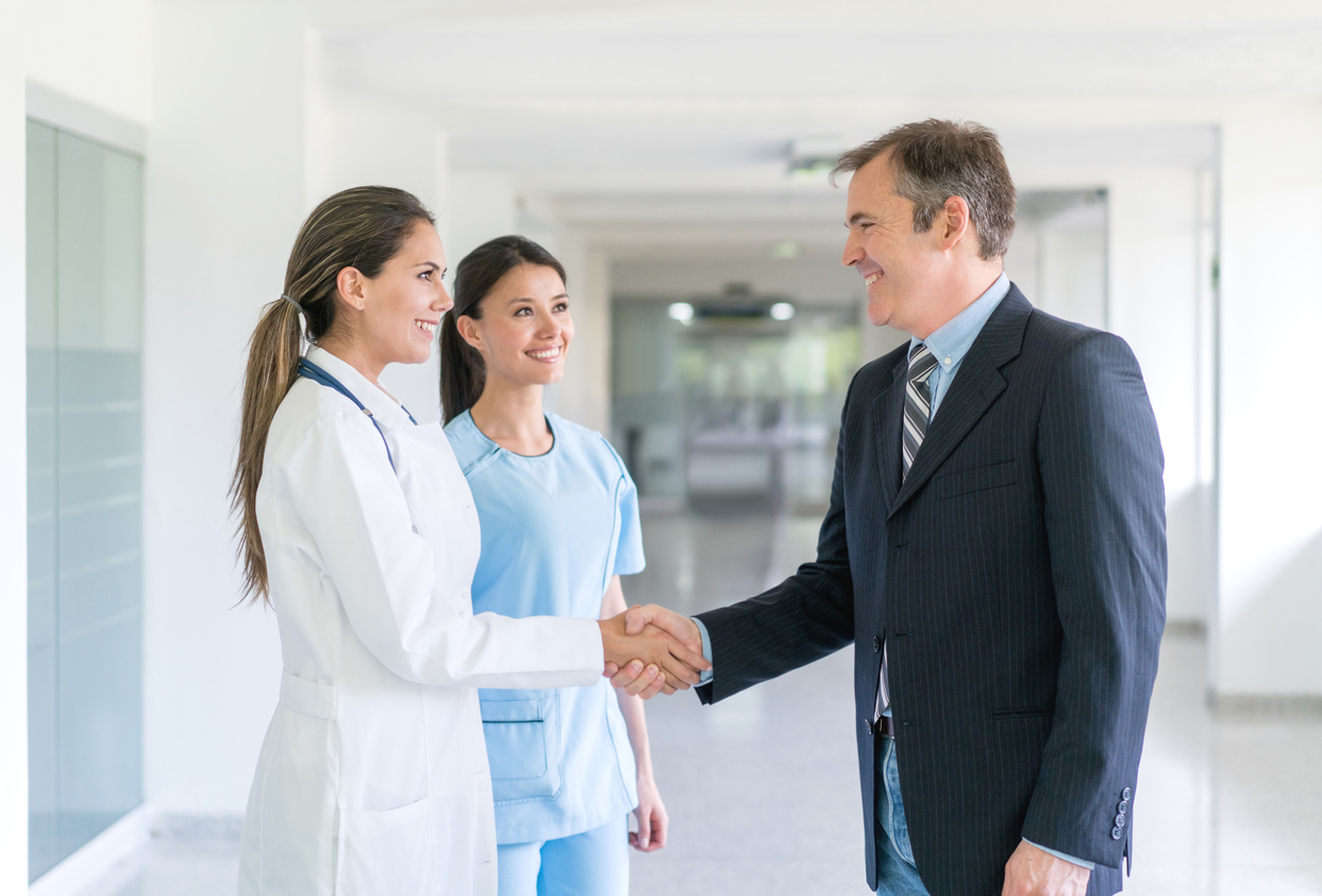 Doctor greeting health insurance agent with a handshake at the hospital