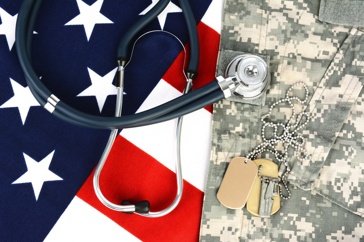 Military dog tags on an American Flag with a stethoscope to illustrate health care in the armed services.
