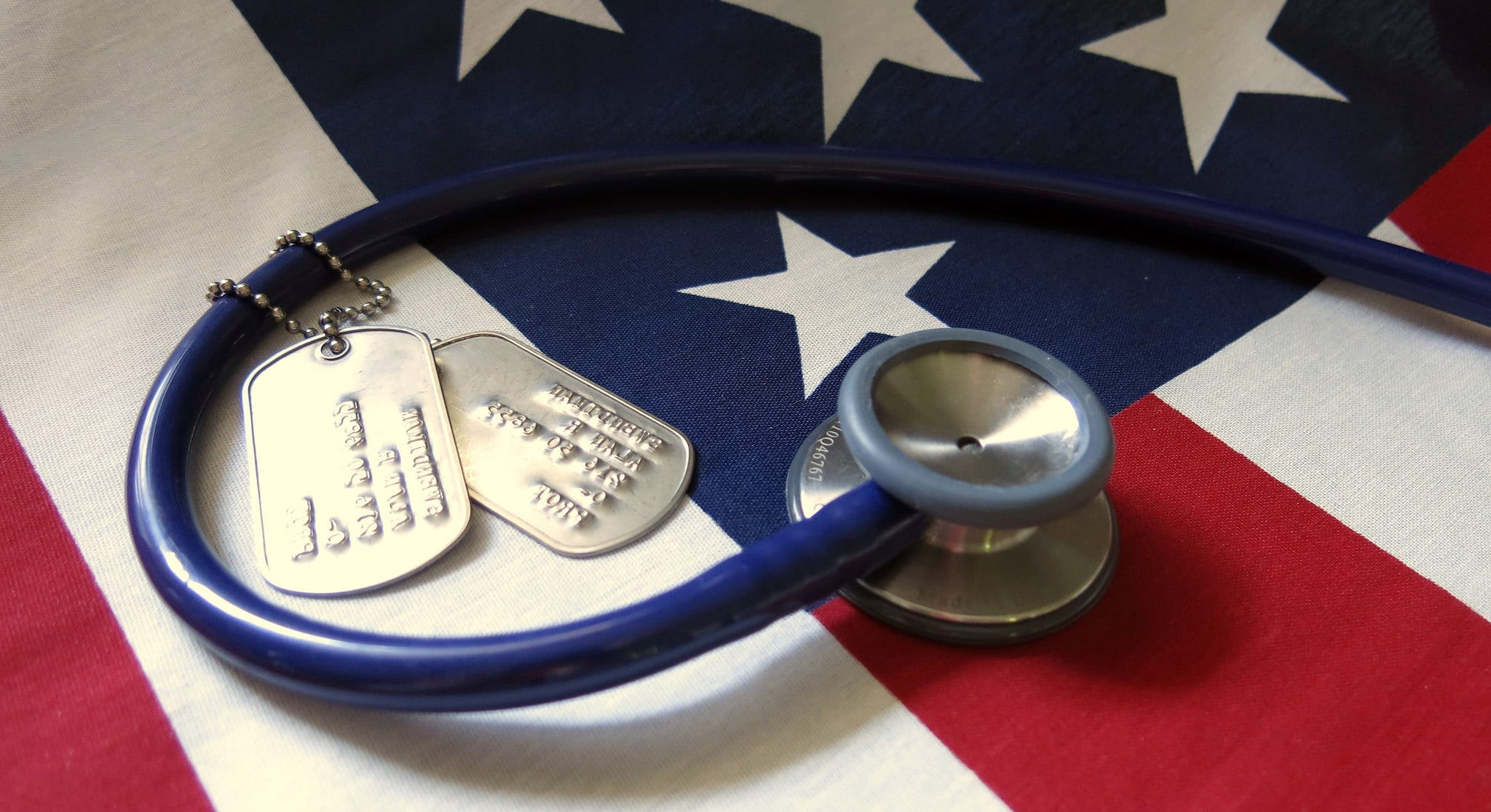 picture of a stethoscope on an American flag with two military dog tags